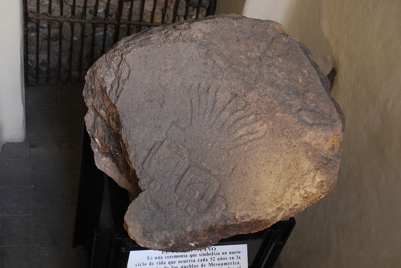 """Image 6. Stone etched with the symbol of the """"new fire"""" or beginning of the 52 year cycle on the Aztec calendar. It is also inscribed with the dates 1 rabbit and 2 serpent. On display at the Palace of Cortes, Cuernavaca, Mexico. Photo by AlejandroLinaresGarcia."""