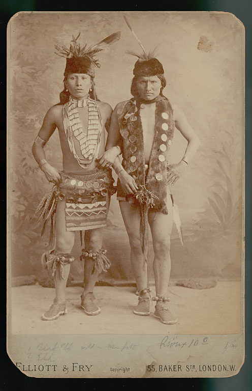 """Image 4. Black Elk and Elk of the Oglala Lakota as grass dancers touring with the Buffalo Bill Wild West Show, London, England, 1887 (source: The Sixth Grandfather: Black Elk's Teachings Given to John G. Neihardt, edited by Raymond J. DeMallie, page 259. The men are wearing """"sheep and sleigh bells; otter fur waist and neck pieces; pheasant feather bustles at the waist; dentalium shell necklaces; and bone hairpipes with colored glass beads...Photograph collected on Pine Ridge Reservation in 1891 by James Mooney. Courtesy National Anthropological Archives, Smithsonian Institution""""). Photo by Elliott & Fry - London, England."""