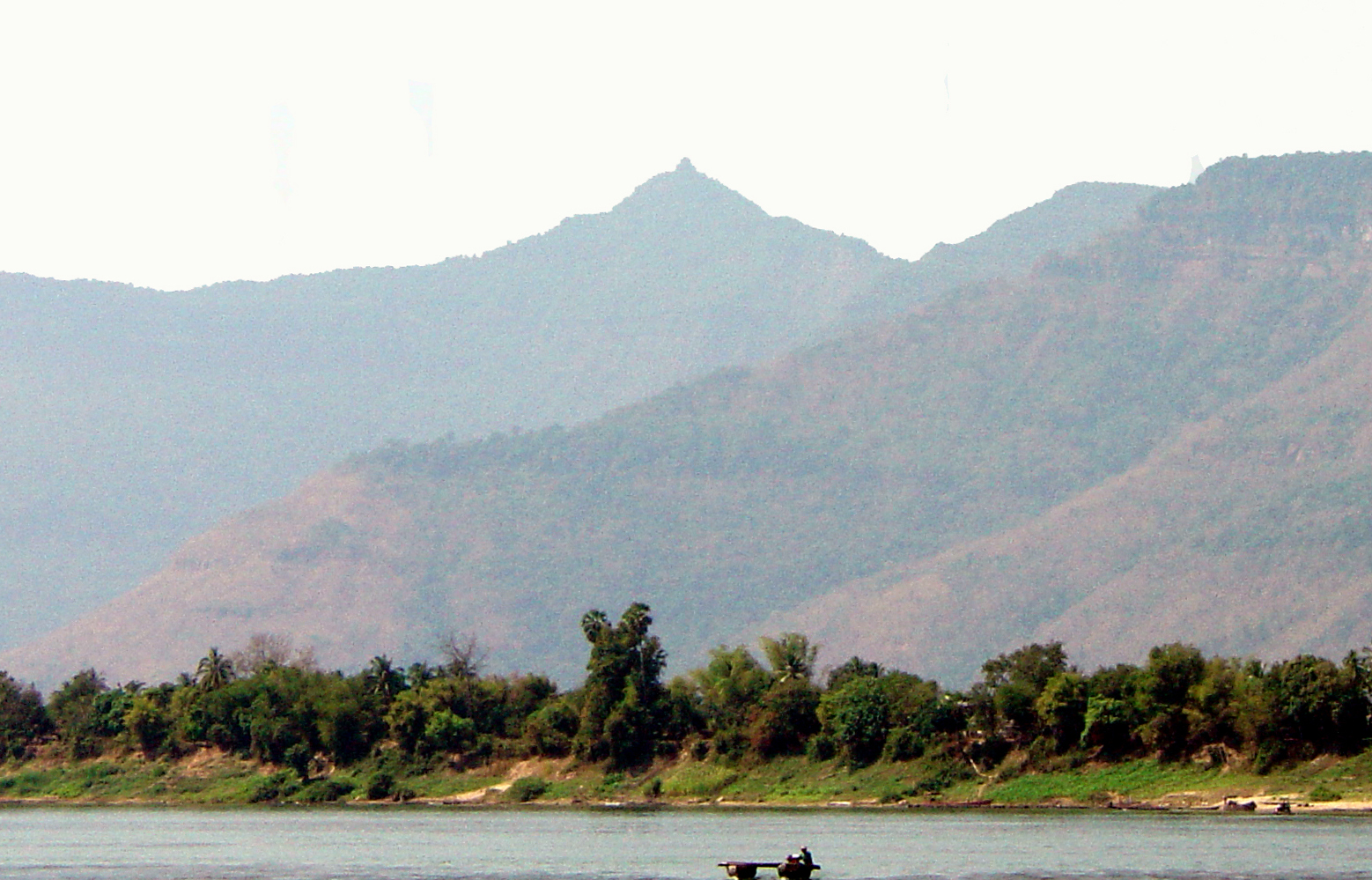 """Image 17. Crossing the Mekong river near Champasak, [Laos] one sees the mountain called """"Lingaparvata [almost certainly = Ling-kia-po-p'o]."""" Wat Phu [a Hindu temple] nestles at the base of this mountain, which has been a sacred site from at least the 5th century A.D., being associated with the early kings of Chela. Photo by Michael Gunther."""