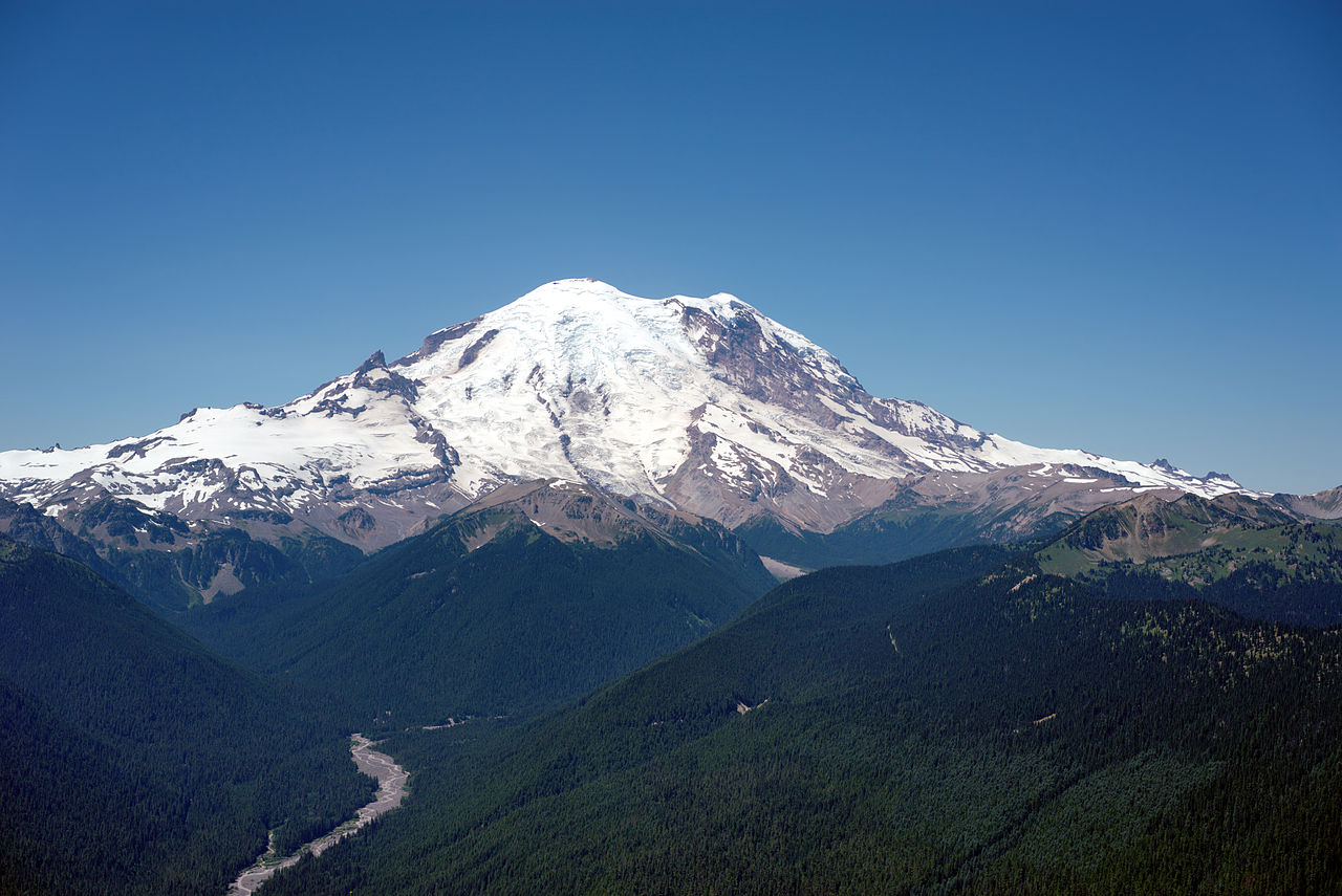 Image 17. Mount Rainier [= Tacoma] as viewed in the summer from Silver Queen Peak, near Crystal Mountain resort at an elevation of around 7000 ft looking west by southwest. The main summit, Columbia Crest (14410 feet) is at the center. The White River is visible in the lower left [Tacoma, Washington, USA]. Photo by Dllu.