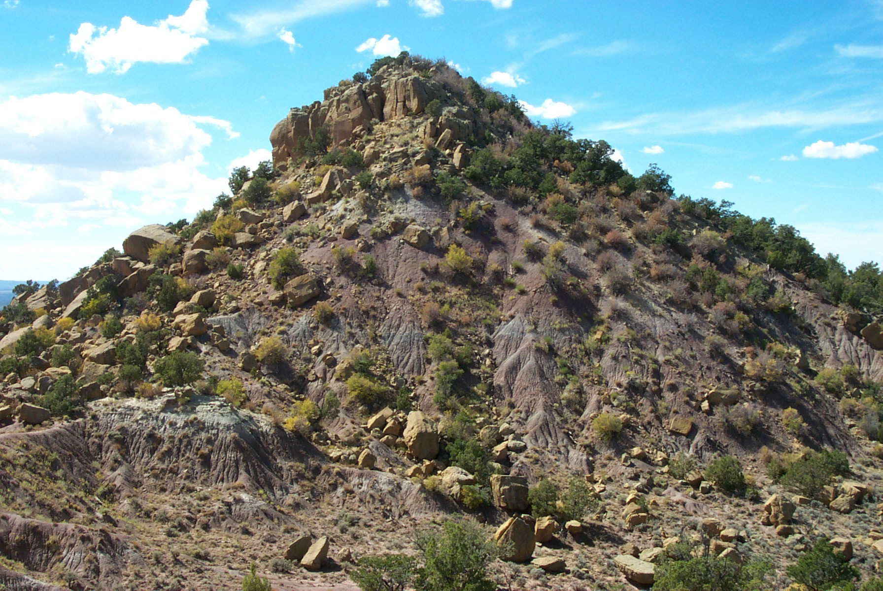 Image 5. Gobernador Knob [Navajo = Ch'óol'į́'í], viewed from the east across the headwaters of Gobernador Canyon. Sandstone caprice boulders armor the slope as they tumble down after the underlying shale is eroded. No trails lead to the summit, but a scramble is possible up the eastern or northern slope. The dominant vegetation in pinion pine, juniper, mountain mahogany, and manzanita [New Mexico, USA]. Permission from the American Geographical Society (http://americangeo.org) and the author/photographer, Kevin Blake (http://www.k-state.edu/geography/kblake/), September 2000.