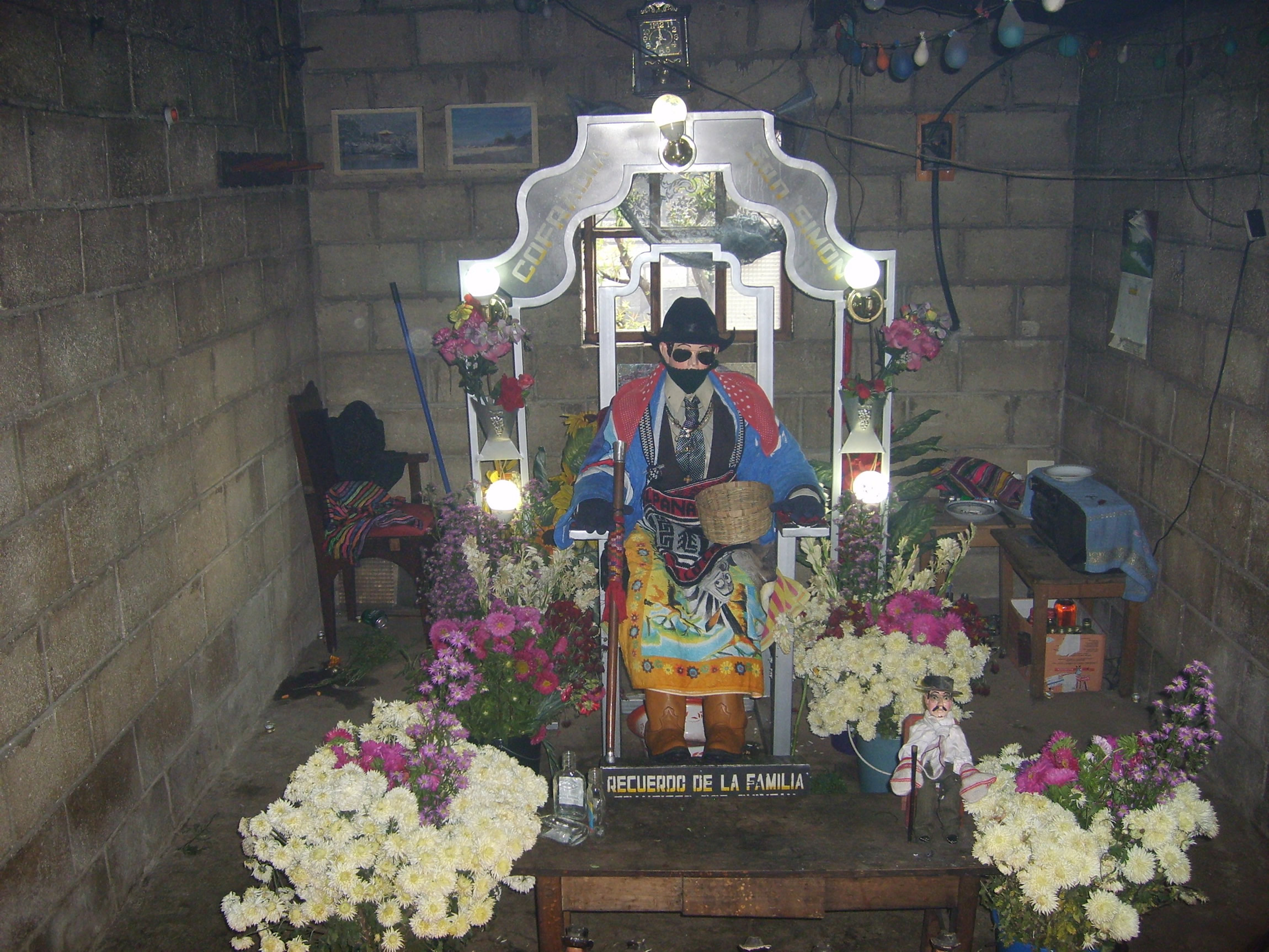Image 11. A lifesize doll of San Simón (Maximón), a Mayan god turned Christian saint [not recognized by the Catholic Church], a subject of veneration in Zunil [a hillside town], Guatemala. The shrine moves from one private house to another every year on November 1. People come to pray there and leave various offerings - usually alcohol and tobacco. The local family takes care of the doll and the shrine during the year, while charging a nominal fee (e.g. 5 GTQ) to visitors. Photo by Sapfan (Jan Petula).