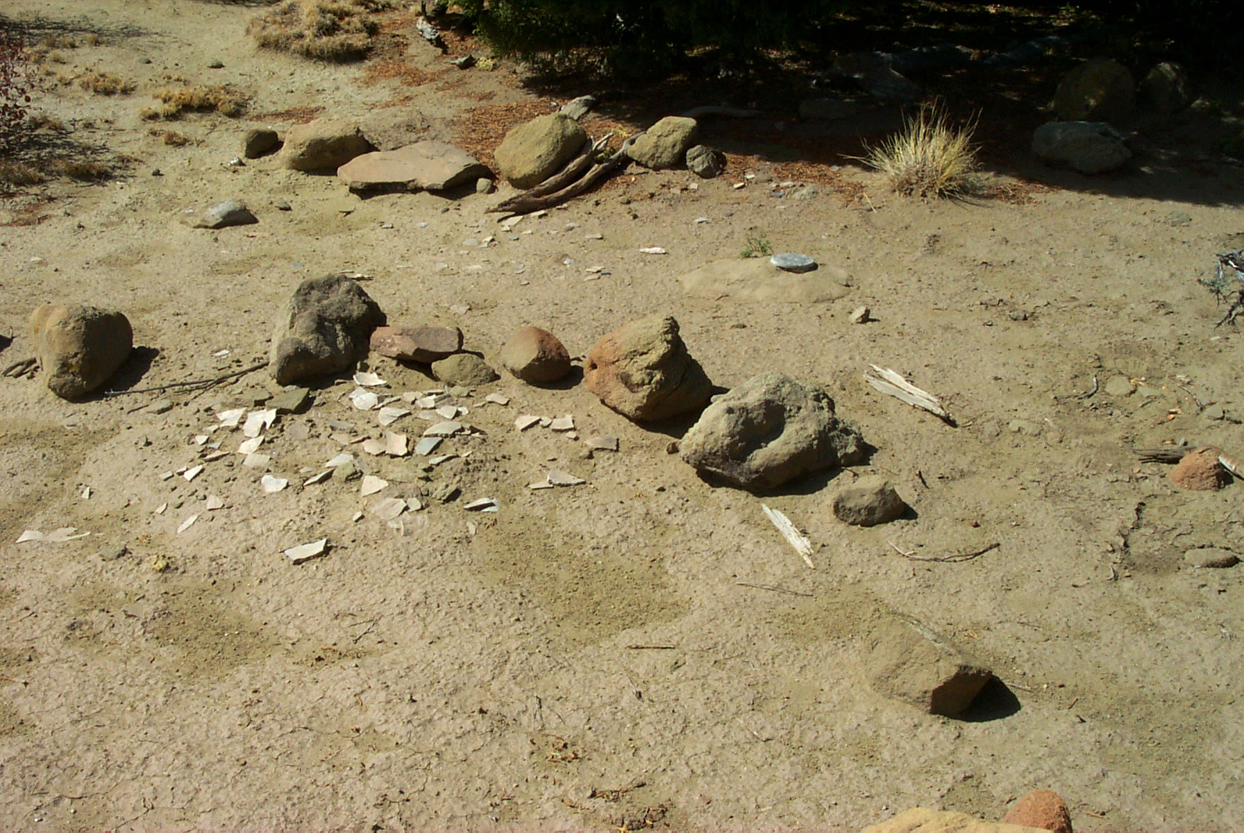 Image 7. Summit of Gobernador Knob with ceremonially arranged pottery shards, stones, and forked stick. The summit benchmark is located in the right center of photo. Permission from the author/photographer, Kevin Blake (http://www.k-state.edu/geography/kblake/), September 2000.